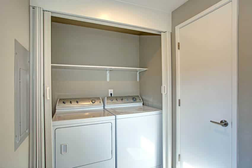 Laundry machine with chute on wall and white door