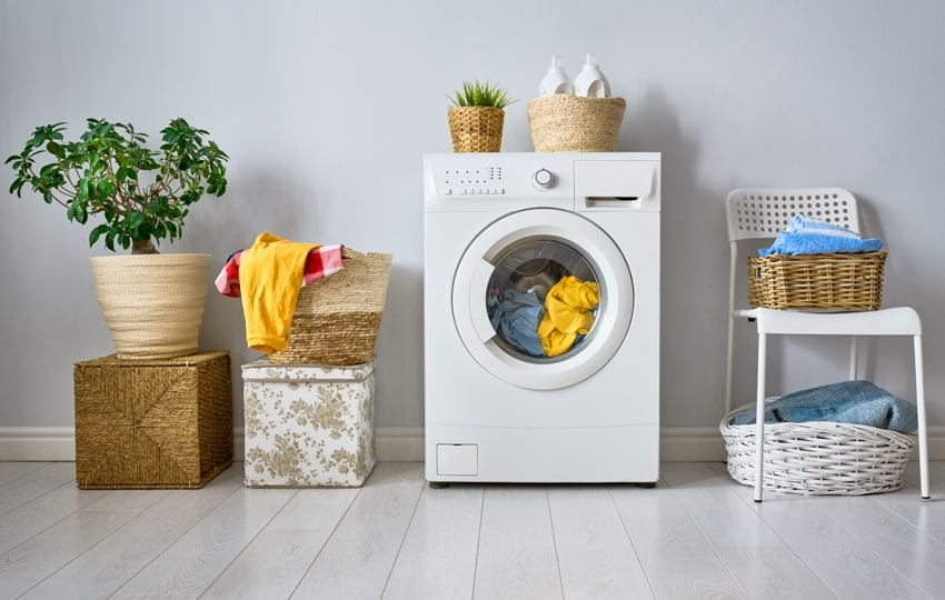 laundry room interior with a washing machine hamper basket green plant and detergents at home
