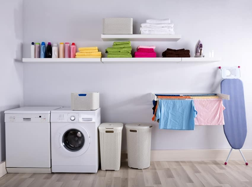 laundry room interior with washing machine ironing body baskets and drying clothes