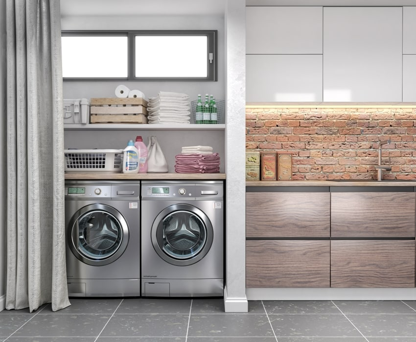 laundry room with tile floor washing machine at closet grey wall shelving and fold clothes