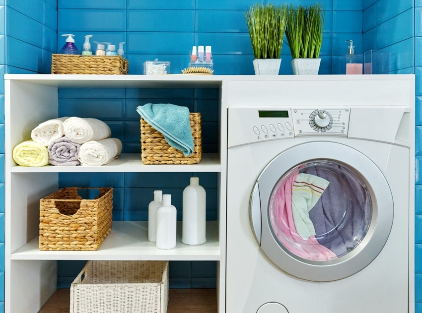 laundry room with white washing machine shelves with supplies and plants