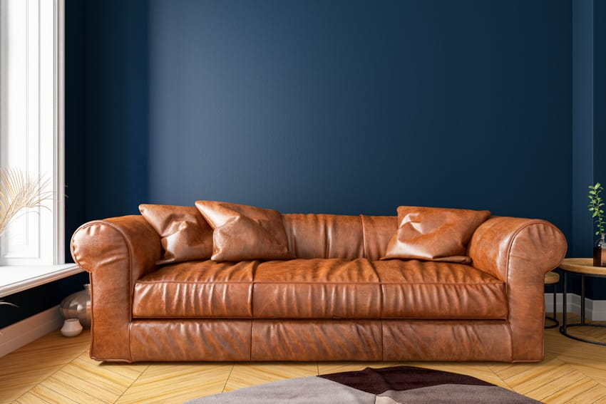 Light brown faux leather sofa blue wall