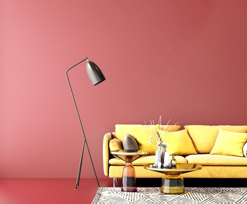 living area with burgundy wall yellow sofa floor lamp cute center table with accent decors on top