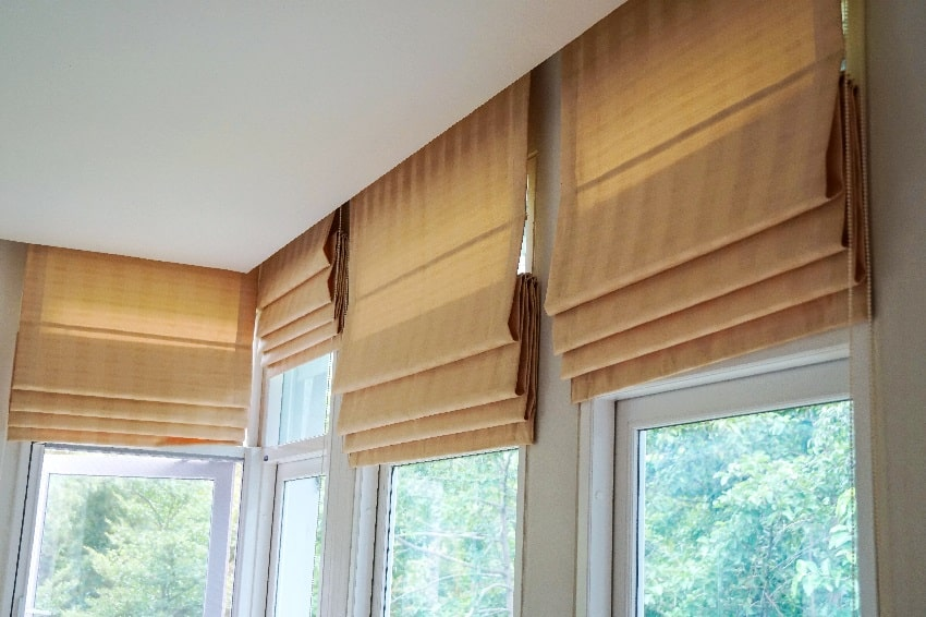 brown roman blind shade curtain and tree forest mountain background