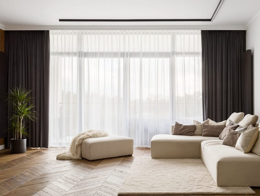 living room with cream white sofa wooden floors with carpet and hanging blackout curtains