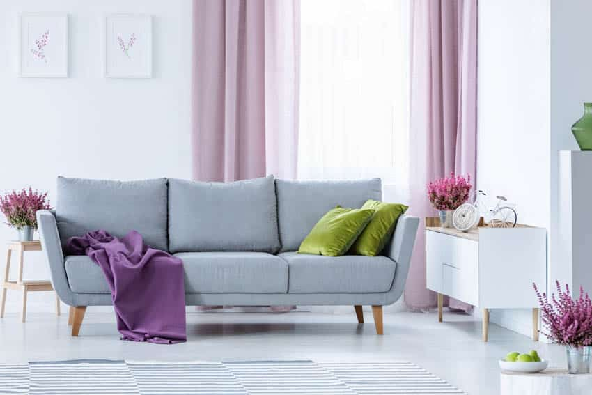 Living room with pink drapes with sheer liner gray sofa