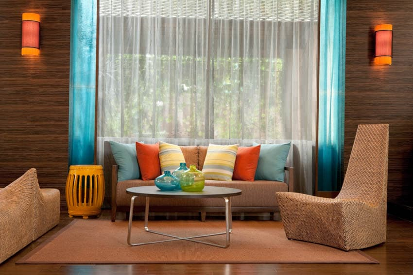 Living room with sofa chairs rug colorful pillows curtains and wall mounted lights