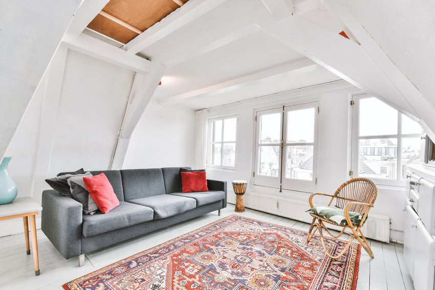 Living room with wicker armchair sofa and persian rug