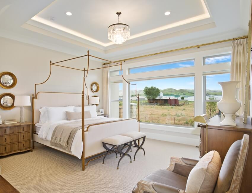 A luxury bright and clean bedroom with Canopy bed footstool and a beautiful view from the window