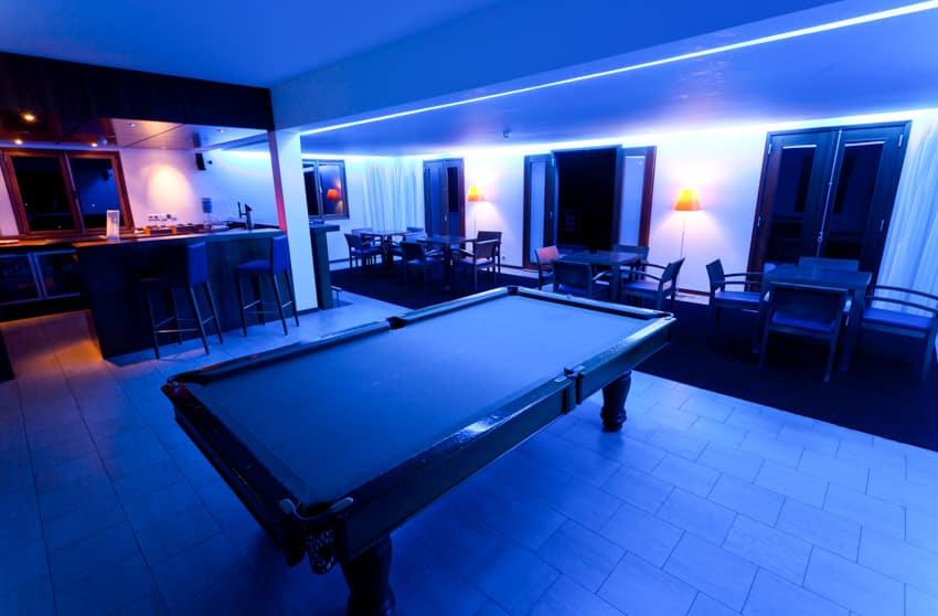 Man cave with bar television billiards table andback lighting