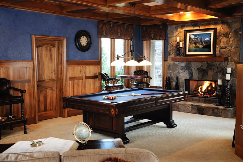 Man cave with color blue wall wood coffered ceiling fireplace and billiards table