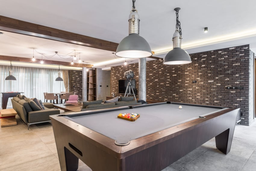 Man cave with gray wall sofa chairs pendant lights and billiards table