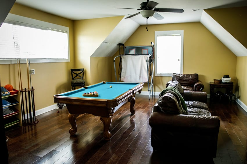 Man cave with wood floor billiards table sofa chairs and ceiling fan