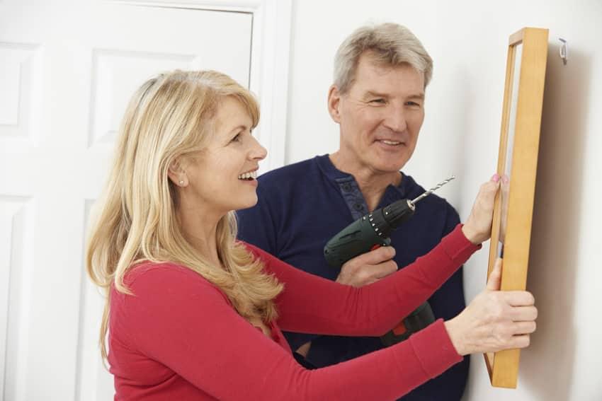 Man drilling wall to hang frame