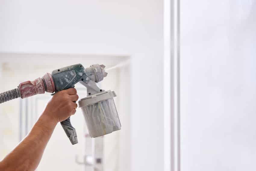 Man painting wall with spray gun