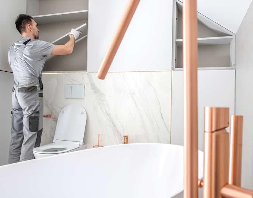 man remodeling closet into bathroom