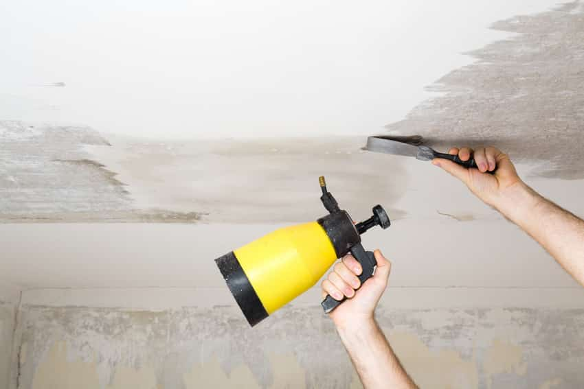 Man removing white chalk from ceiling with scraper and sprayer