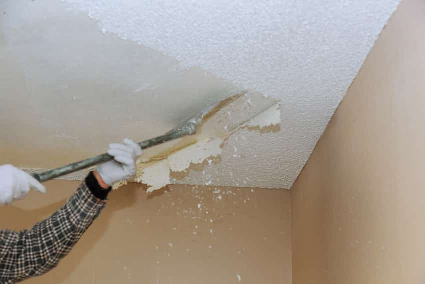 Man scrapping a popcorn ceiling