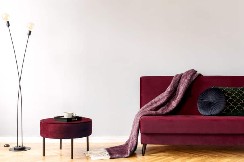 minimalistic home interior with gray wall burgundy velvet design sofa and pouf black lamp