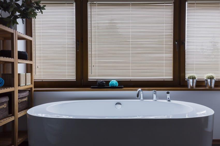 Modern bathtub in bathroom with blinds
