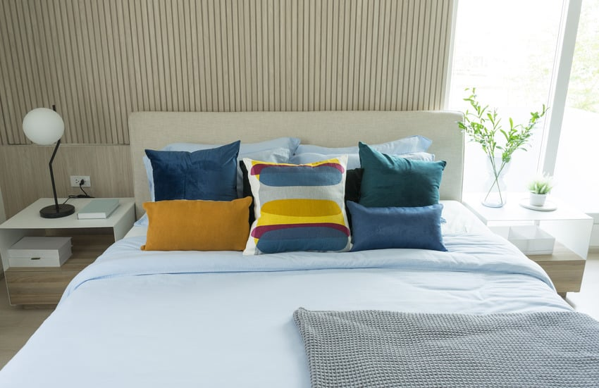Modern bedroom interior with blue and yellow pillows
