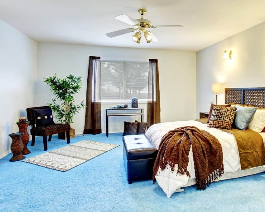 Modern bedroom interior with blue carpet floor wooden furniture and brown curtains