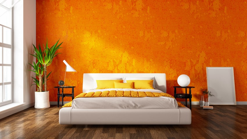 Modern bedroom interior with orange walls pillows and wooden flooring