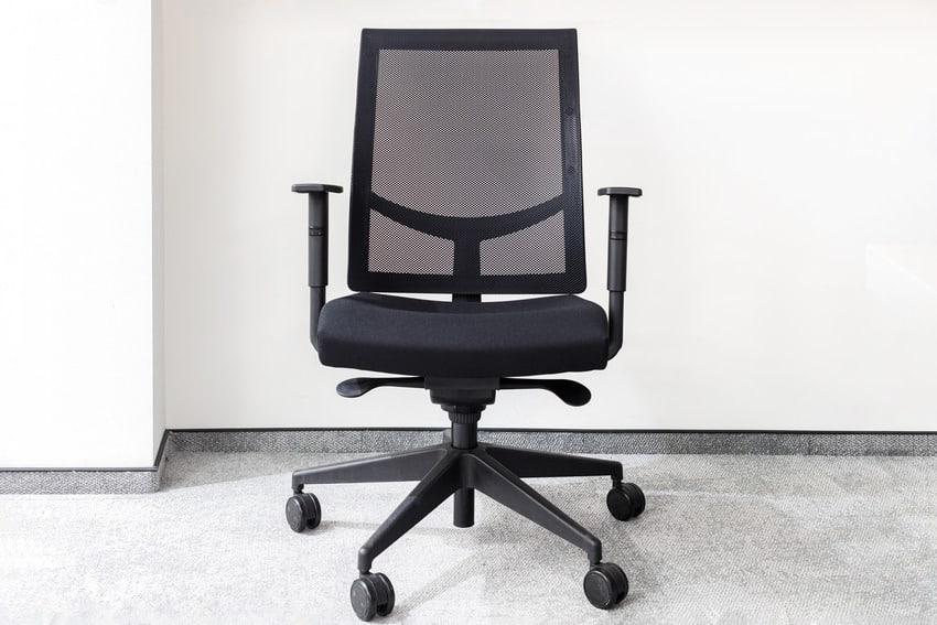 Modern black ergonomic office chair in empty room