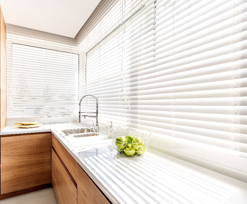 modern bright kitchen interior with white horizontal window blinds wooden cabinets with white countertop