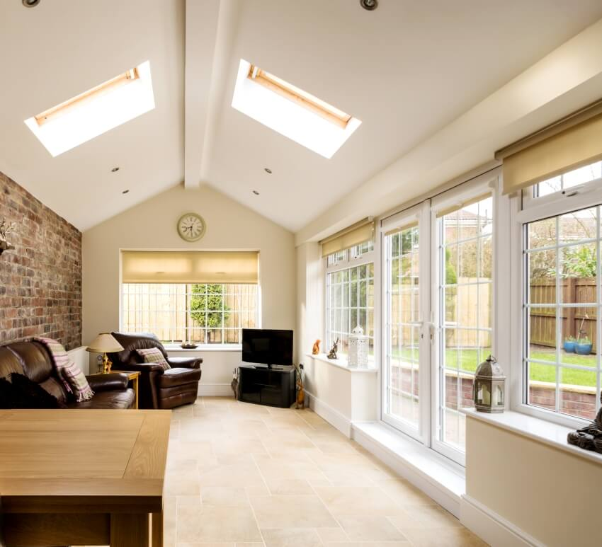 Modern conservatory sunroom extending into the garden with a featured brick wall