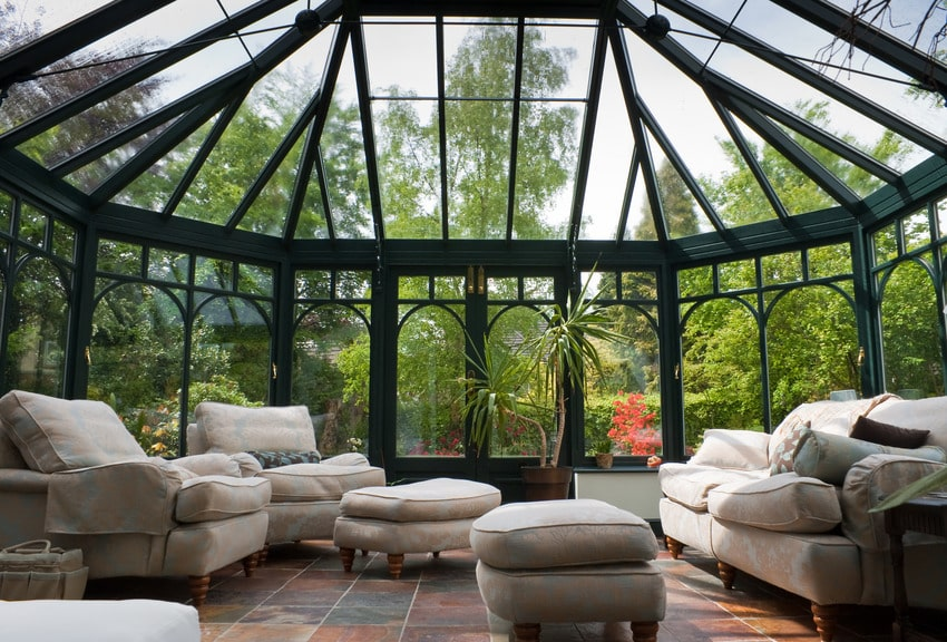 Modern conservatory with cozy furniture and refreshing nature view