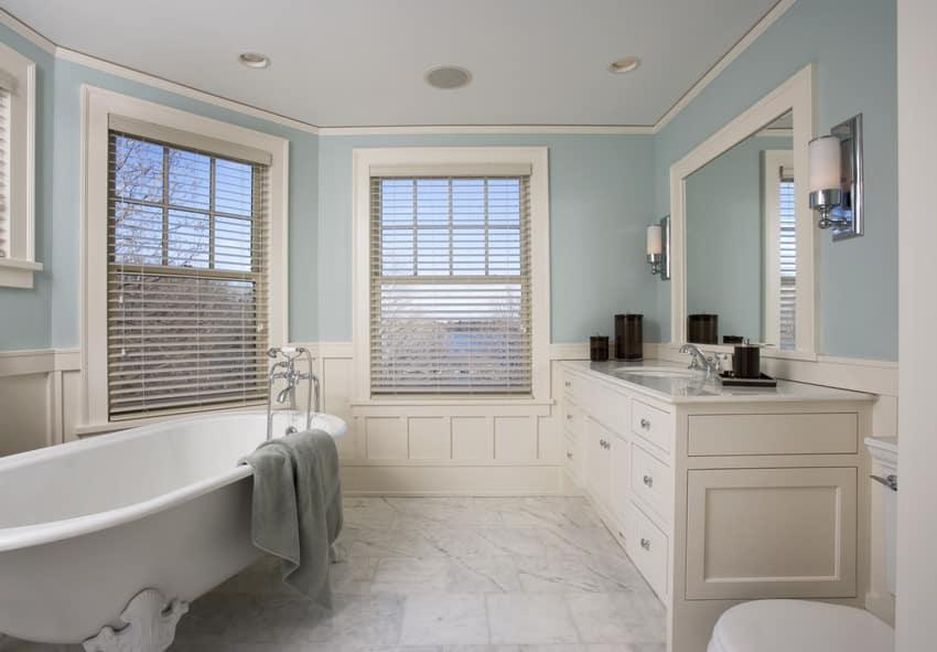 Modern cozy bathroom with pale blue walls bathtub and sink