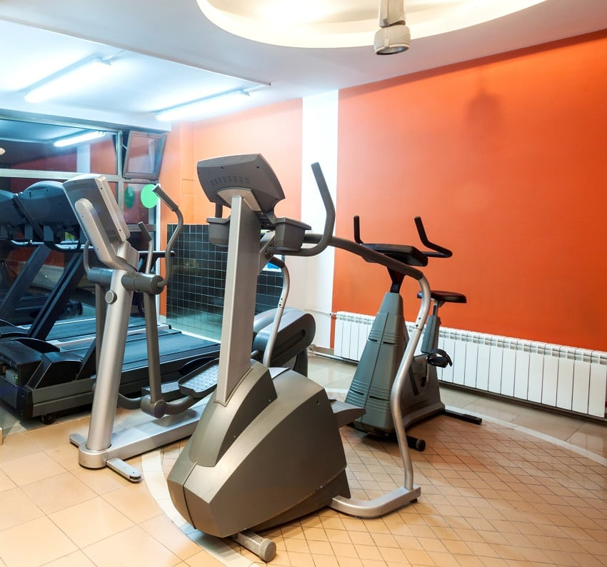 modern gym interior with equipment with orange wall paint