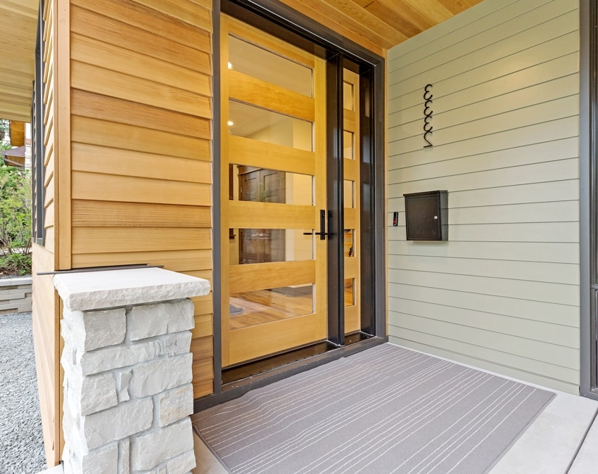 modern home with glass paneled front door and beautiful composite shiplap siding