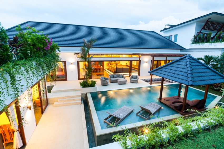 Modern house with large glass windows pool lounge chairs patio outdoor furniture