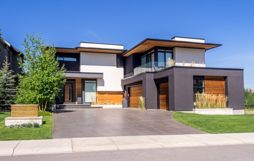 Modern house with spacious stained concrete finish driveway wood siding