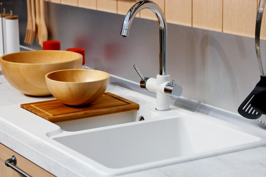 Modern kitchen interior with wooden bowl on chopping board faucet and sink on foreground