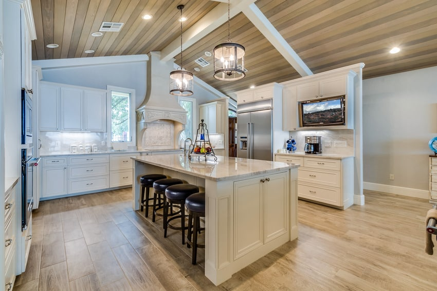Modern kitchen interior with beige paint, wooden flooring and light fixtures