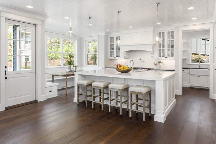 Modern kitchen with center island white stools dining booth area near window door and ceiling lights