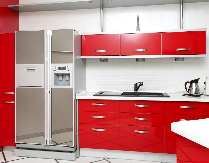 Modern kitchen with red cabinets white walls and gray fridge