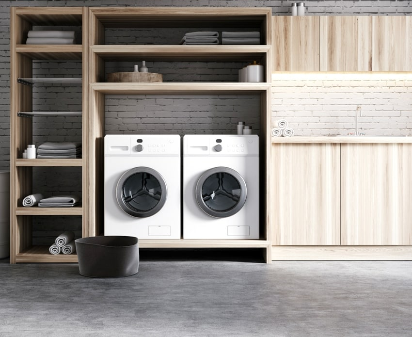 modern laundry room interior with white brick walls concrete floors wooden consoles and shelves with two white washing machines