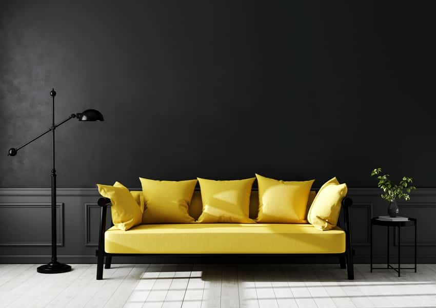Modern living room with black wall a yellow sofa and black lamp and table