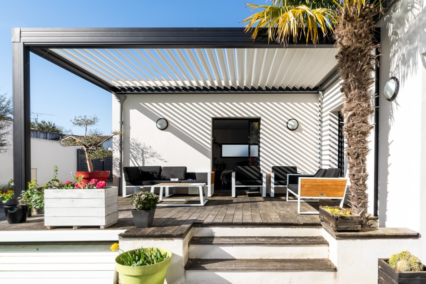 Modern pergola with louvered roof and furniture on wood patio