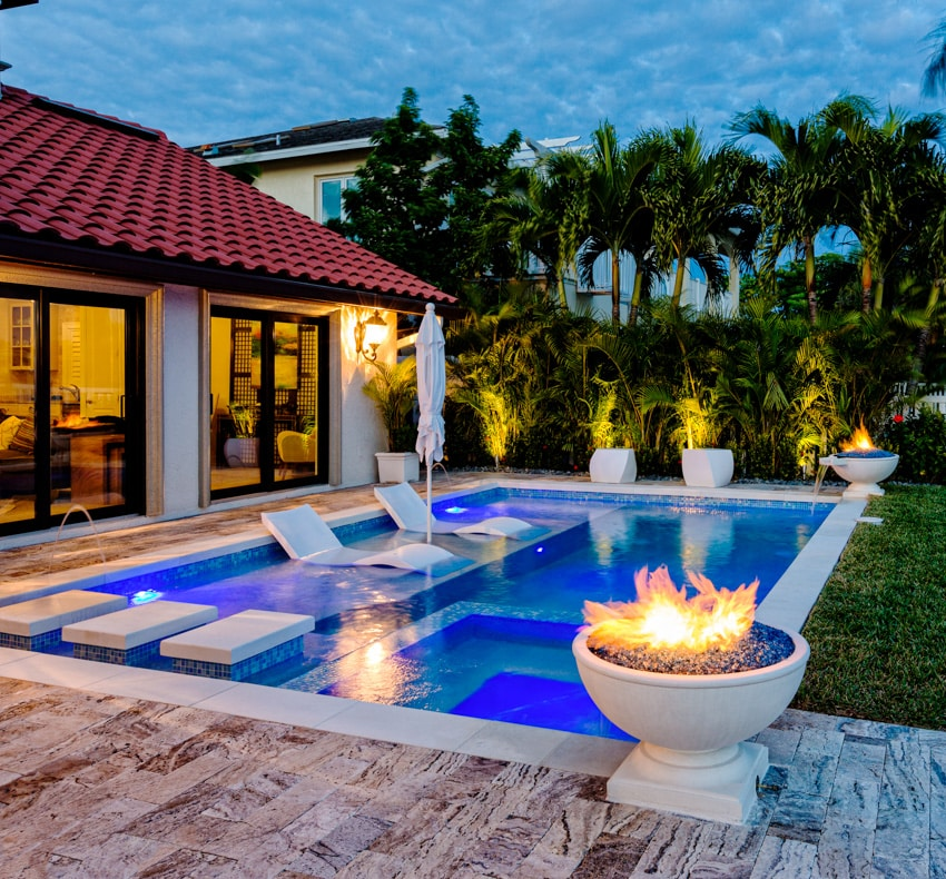 Modern pool with fire pit ledge and lounge chairs