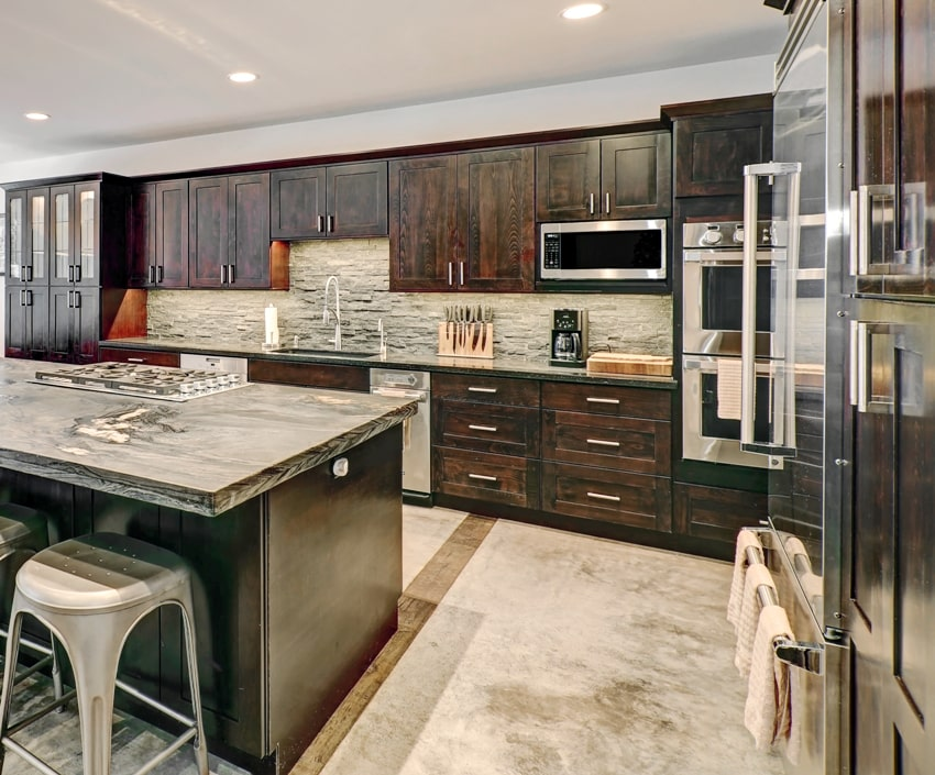 Modern traditional american kitchen design in grey tones with dark wood storage and center island with stone counter top