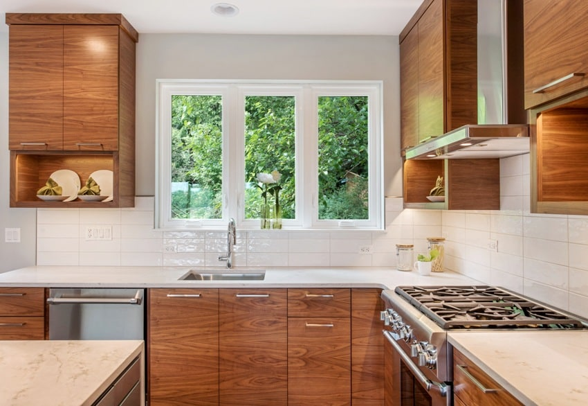 Modern wood cabinets in beautiful kitchen kitchen hood and gas range with sink nearby