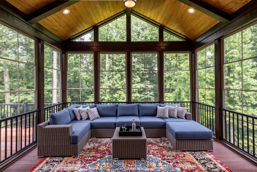 Newly furnished enclosed porch with cozy sofa and decorative pillows