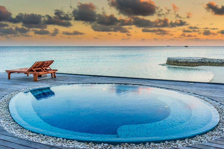 Oceanfront wading circular pool with ledge and lounge chair
