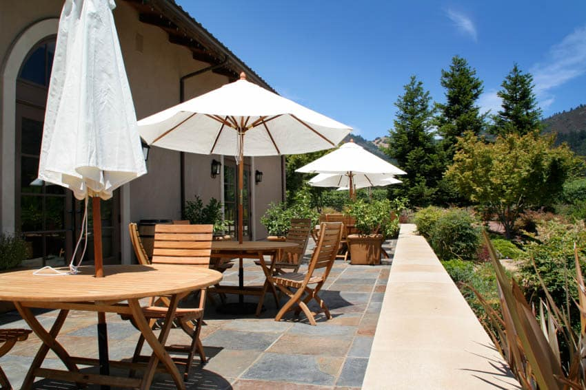 Outdoor patio with wooden chairs and tables slate tiles