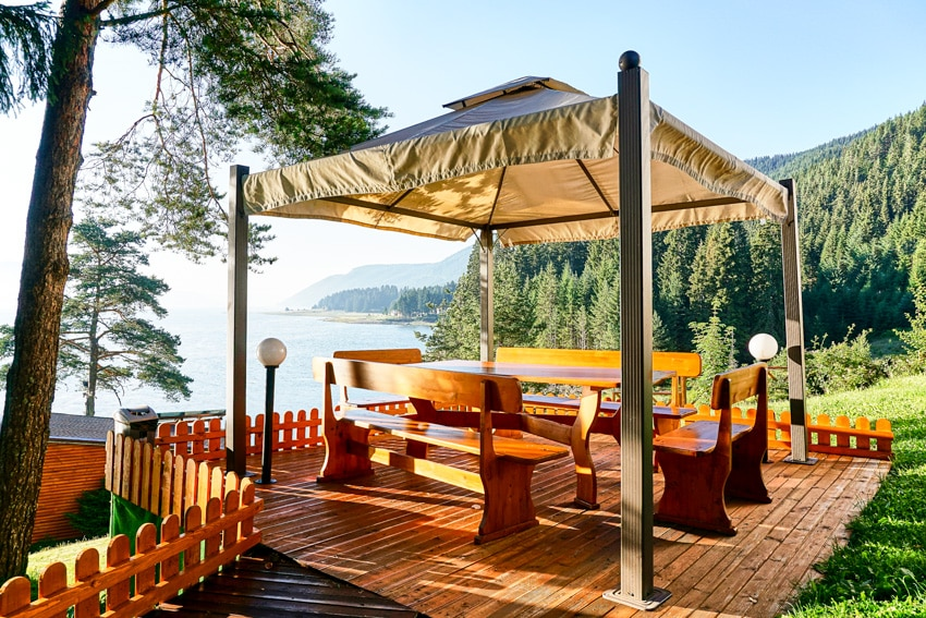 Outdoor wooden deck with canopy and furniture